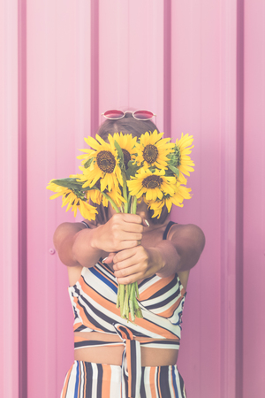 Fashionable woman covering her face with sunflowers against rose wall.