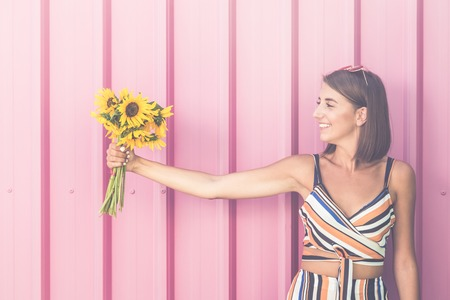 Beautiful young girl holding sunflower bouquet against rose colored wall outdoors. Reklamní fotografie
