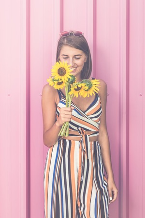 Cheerful girl holding bouquet of sunflowers against pink color background. Reklamní fotografie