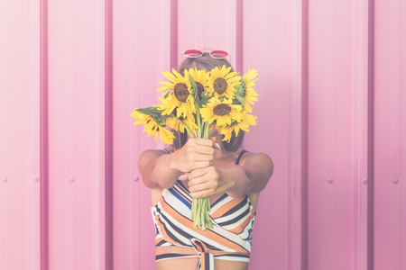 Hipster girl holding bouquet of sunflowers over her face on pastel pink background.