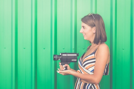 Hipster woman holding retro video film camera on green background.