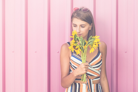 Portrait of hipster girl holding bouquet of sunflowers on pink background. Space for copy.