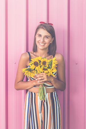 Portrait of happy woman with sunflowers bouquet against rose wall outdoors.