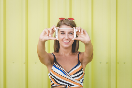 Portrait of young fashionable woman taking selfie with smartphone on yellow background. Reklamní fotografie