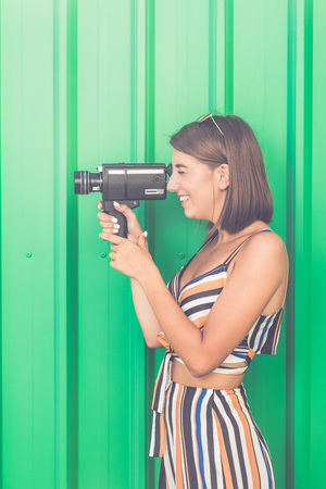 Beautiful modern girl with old 8mm camera.