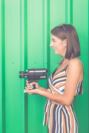 Young fashionable girl with vintage camcorder against green wall outdoors.