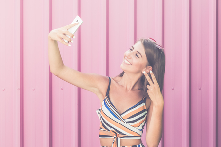 Modern girl taking self portrait with her smart phone against pink background. 版權商用圖片
