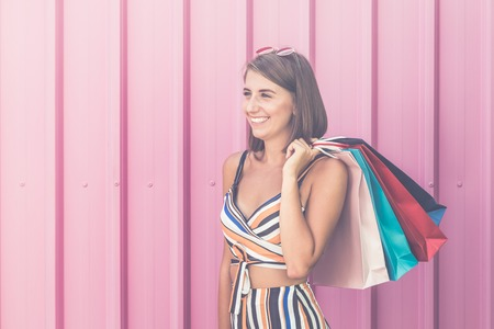 Fashionable woman holding colorful shopping bags on pink background. Space for copy. Reklamní fotografie