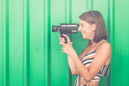 Woman recording. Side portrait of young person capturing video with retro film camera.