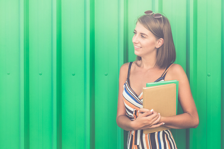Young fashionable student holding colorful books on green background. Space for copy.