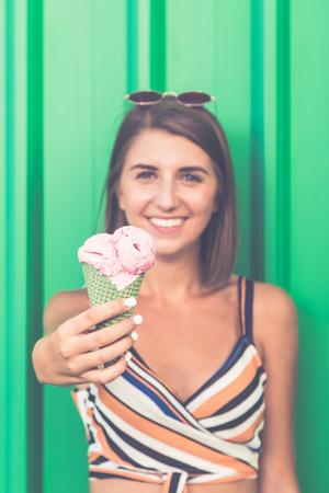 Close up of young girl holding ice cream against green background.