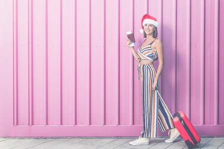 Fashionable woman wearing santa hat, holding suitcase and passport with tickets on pastel pink background. Reklamní fotografie