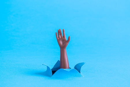 Black doll arm emerging from blue paper background. Drowning minimal creative abstract concept.