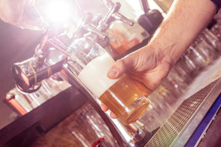 Close up of barman pouring lager beer in drinking glass.