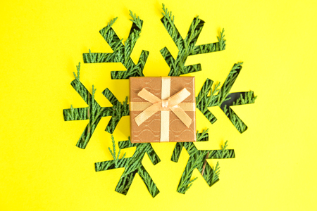 Present and snowflake with christmas tree branches on yellow background minimal creative holiday concept. 版權商用圖片