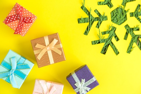 Presents and snowflake with christmas tree branches on yellow background minimal creative holiday concept.