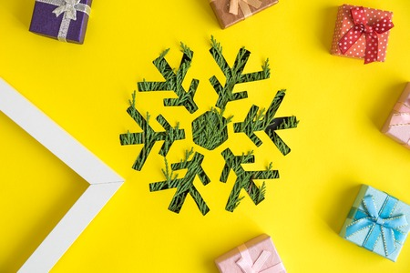 Snowflake with Christmas tree branches, gift boxes and photo frame against yellow background minimal creative holiday concept.