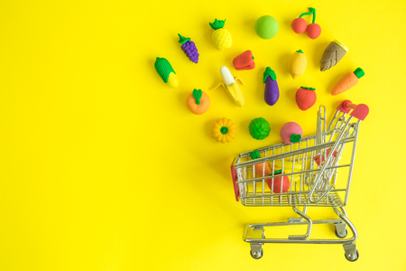 Creative layout shopping cart with rubber vegetables and fruits on yellow background minimal creative concept. Space for copy.