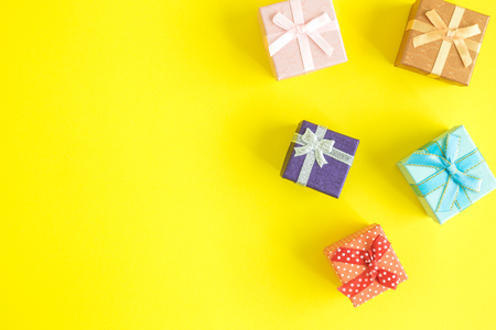 Flat lay of colorful gift boxes on yellow background. Space for copy. 版權商用圖片