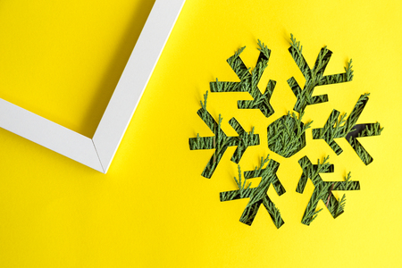 Snowflake with Christmas tree branches and photo frame on yellow background minimal creative holiday concept.
