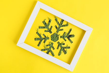 Snowflake with Christmas tree branches and photo frame against yellow background minimal creative holiday concept. 版權商用圖片