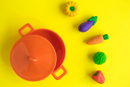 Flat lay of rubber vegetables and cooking pot on yellow background minimal creative concept.