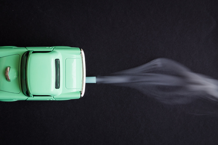 Flat lay of car toy emitting smoke CO2 from exhaust pipe on dark background minimal creative concept. 版權商用圖片