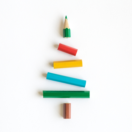 Flat lay of multicolored pencils in form of Christmas tree abstract on bright background.