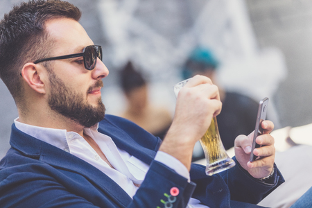 Close up portrait of modern businessman holding glass of beer and using mobile phone in outdoor cafe.