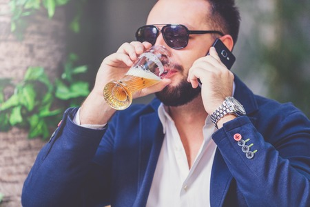 Close up portrait of modern businessman drinking beer and talking on the mobile phone.