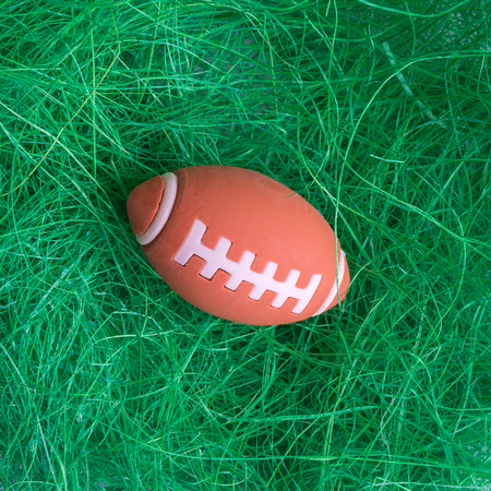 American football ball on green grass minimal creative sport concept. 版權商用圖片