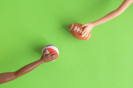 Close up of doll hands holding american football and basketball balls on green background minimal creative concept. 版權商用圖片