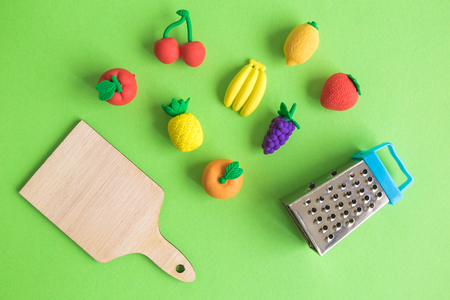Top view abstract of fruits, wooden cutting board and grater isolated on green minimal creative concept.