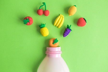 Flying or falling fruits model toys and bottle of smoothie on green background minimal creative concept.