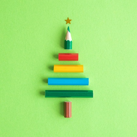 Christmas tree made of colorful pencils on pastel green background minimal holiday creative concept. 版權商用圖片