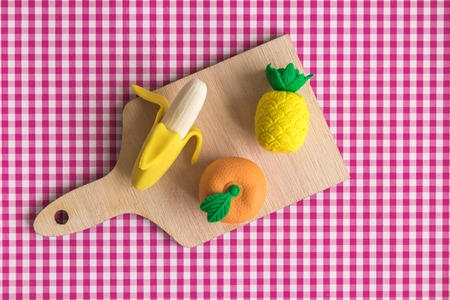 Top view of tropical fruit model toys on wooden cutting board on table minimal creative concept.