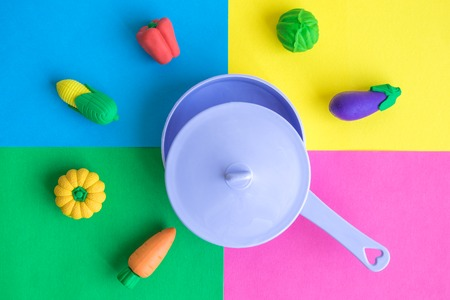 Vegetables and saucepan abstract against multicolored background.