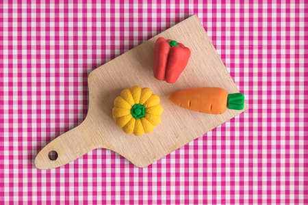 Top view of vegetable model toys on wooden cutting board on table minimal creative concept.
