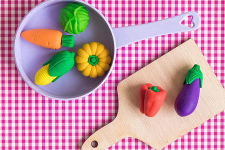 Top view of vegetable model toys on wooden cutting board and plastic pan on table minimal creative concept.