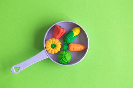Rubber vegetables in plastic pan on pastel green background minimal creative concept. 版權商用圖片