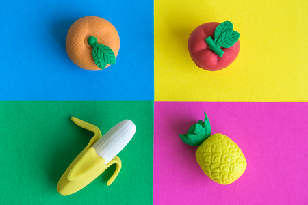 Flat lay of fruit toys against multicolored background.