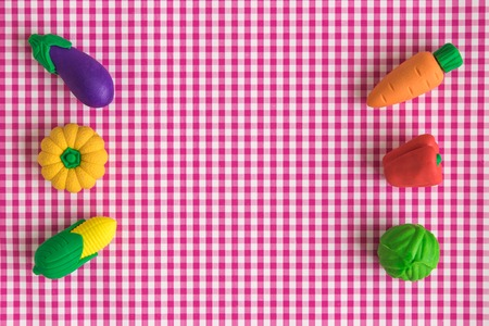 Flat lay of vegetable toys on red classic checkered tablecloth texture minimal creative concept. Space for copy.