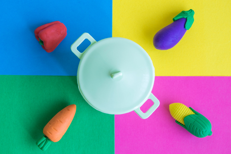 Flat lay of plastic pot with various rubber toy vegetables on colorful background minimal creative concept.