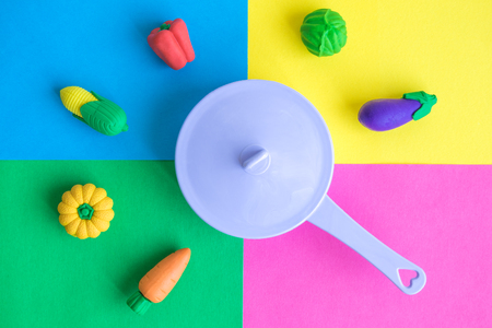 Flat lay of plastic pan with various rubber toy vegetables on colorful background minimal creative concept. 版權商用圖片