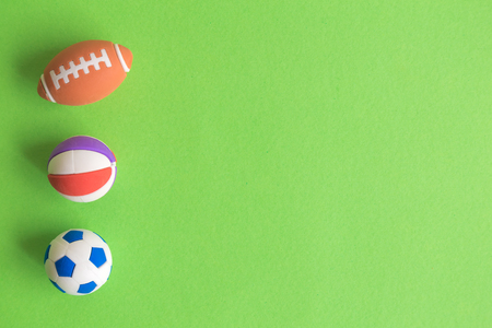 Flat lay of sport balls toys on pastel green background minimal creative concept. Space for copy.