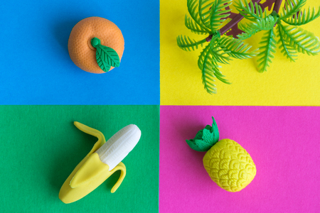 Tropical rubber fruits and plastic palm tree on colorful background.