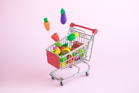 Vegetables falling in shopping cart on pastel pink background minimal creative concept.