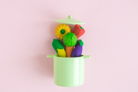 Vegetables falling in kitchen cooking casserole pot abstract isolated on rose.