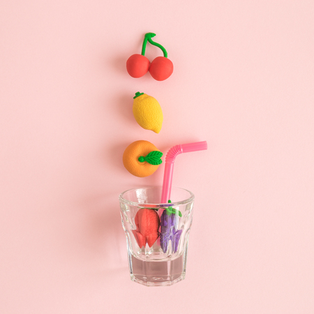 Flat lay of fruit toys falling in drinking glass on pastel pink background minimal healthy food creative concept.