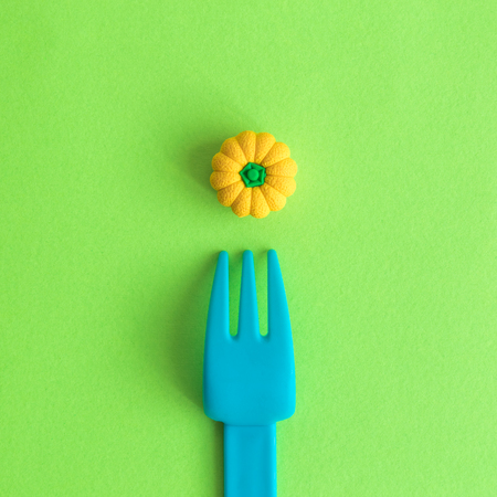 Flat lay of plastic fork and small rubber squash toy against green background minimal creative vegetarian concept.